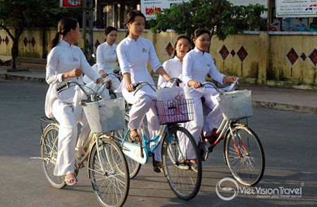 The school girl go to school in ao dai the traditional dress in Hoi An