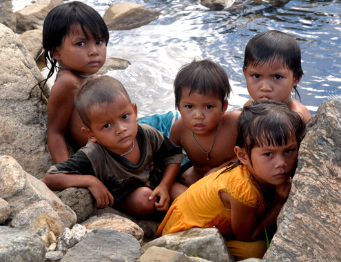 Roads way back, these kids sitting by the stream shrinking the bewildered eyes of fear mixed strangers to the village.