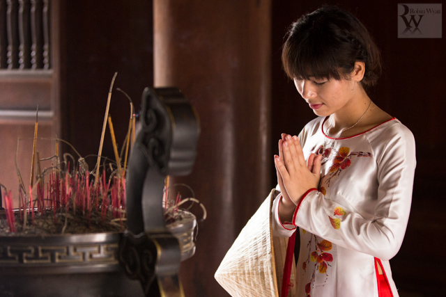 A young Vietnamese student offers prayers for success in her studies at Hanoi's Temple of Literature.