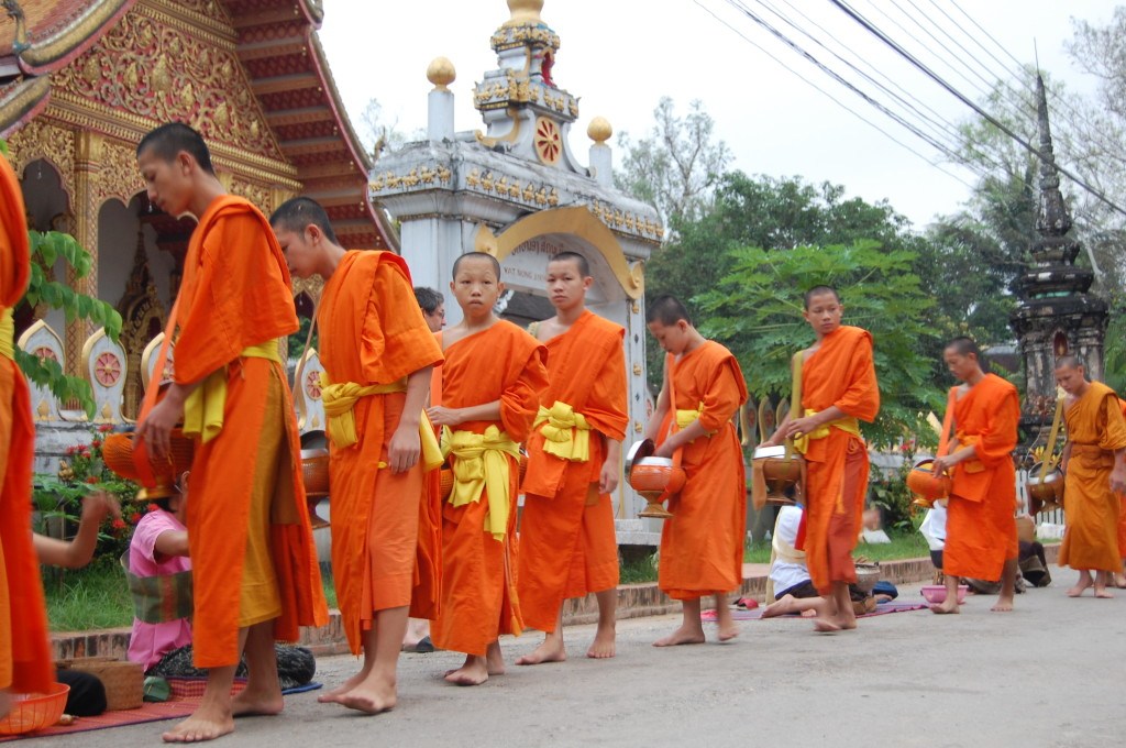 Luang Prabang Buddhist monks collecting alms on street, Laos.