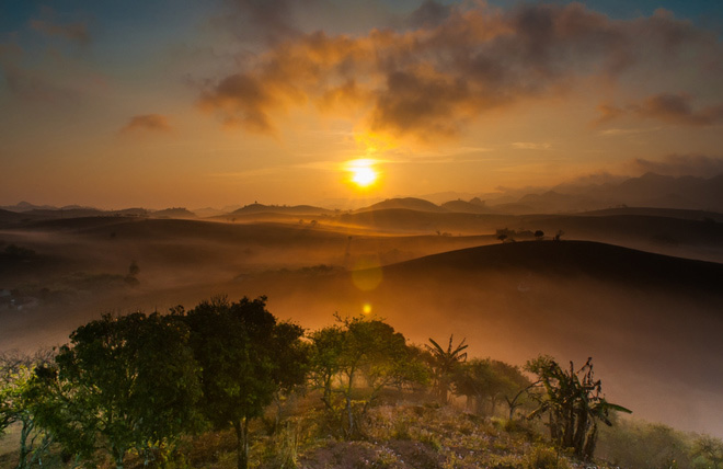 When the sun rise over the hill is the time when you clearly see the thin layer of fog covers the hills. Sunbeamss of a new day make the mist gradually dissolves creating beautiful landscapes.