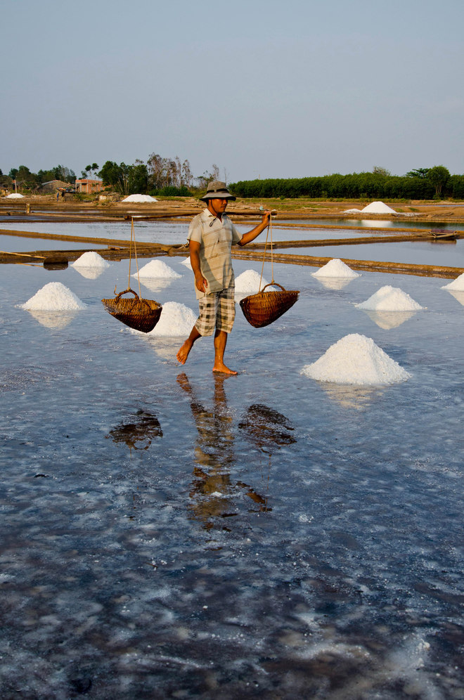 With experience of salt here is just enough time for the salt to crystallize out on the field. Now they will use the earthing salt into small mounds for easy collection.