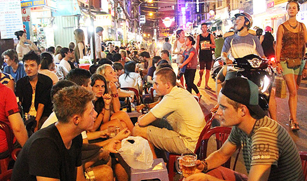 Foreign tourists drink beer and eat street food in the 'Westerners' Town' in District 1, Ho Chi Minh City