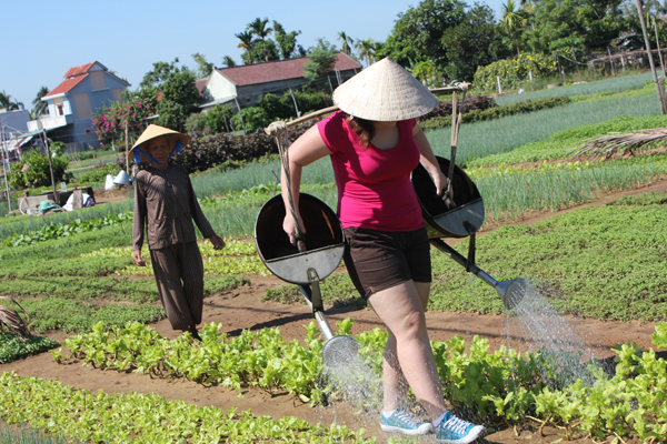 Traveler watering vegetable in Tra Que Village