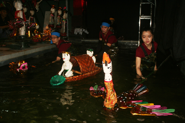 A couple of fisherfolk are aboard a bamboo boat vietnamese water puppetry