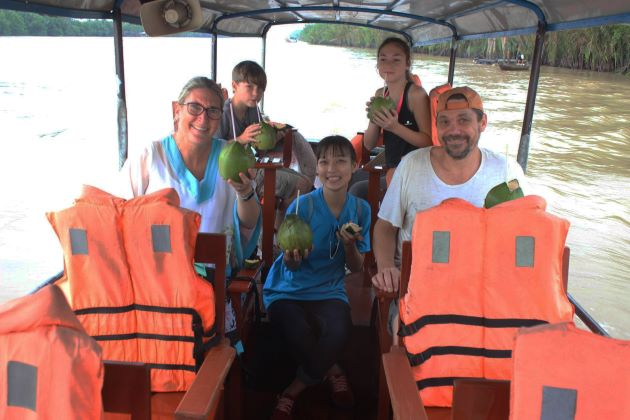 a family on boat trip at mekong delta