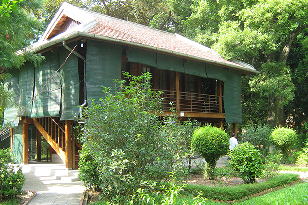ho chi minh stilt house surrounded by a green garden