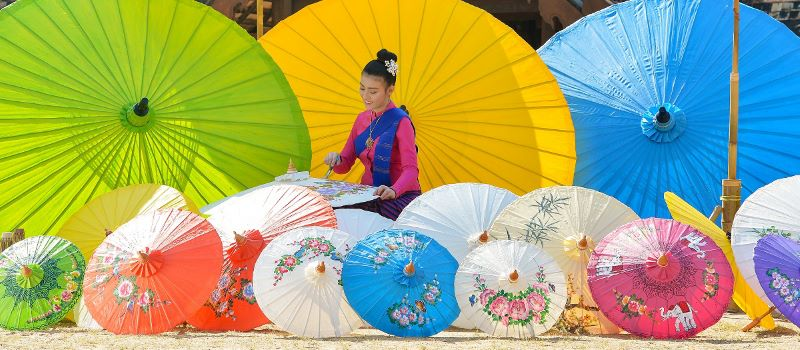 women with umbrellas in bangkok thailand vietnam cambodia tour packages