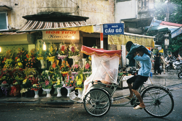 A cyclo go through a rainy day in Cau Go Street Hanoi Old Quarter