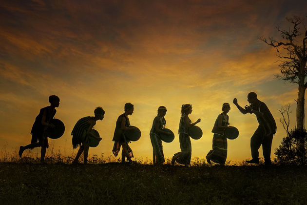 Old ethnic man training his students playing Gong - Central Highlands of Vietnam