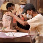 Artisans carving the Buddha statue at Artisans d'Angkor