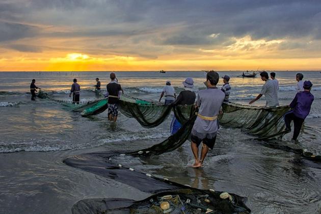 Fishermen casting fishing net at dawn in My Khe Beach