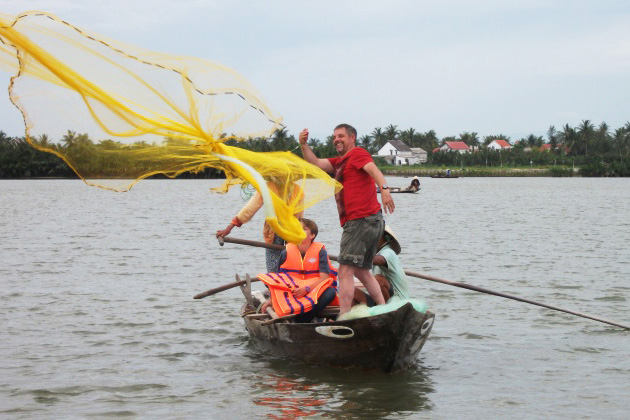 Tourist casting net fishing in Hoi An