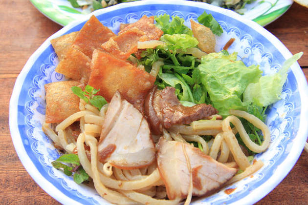 cao lau yellow noodles with pork and greens
