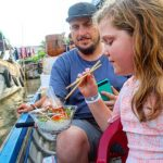 enjoy food on boat at a floating market in mekong delta on a family vacation in vietnam