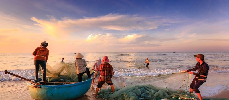 dawn at the beach with fishermen
