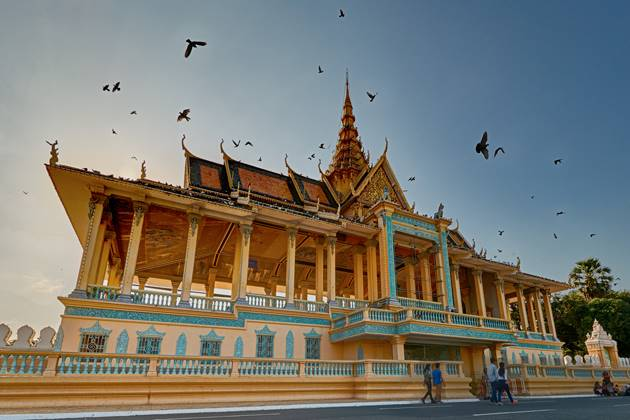Peaceful birds fly over Royal Palace in Phnom Penh