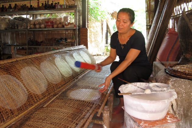 local woman making rice paper in a traditional way